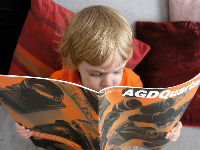child reading the agd quarterly magazine - brian switzer, esther mildenberger, envision+