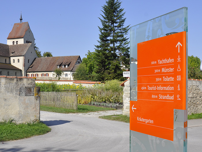 directional sign on glass behind the historic münster of reichenau - brian switzer, envision+